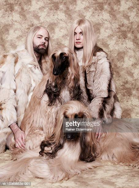 Couple with long blond hair sitting with two Afgan Hounds in studio, portrait
