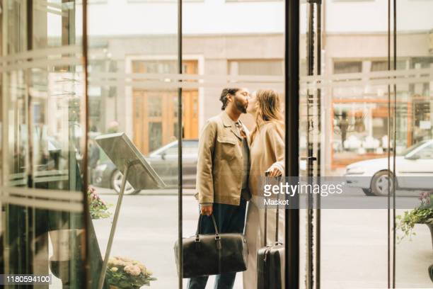 couple with luggage kissing while standing at entrance of hotel - kussen met de mond stockfoto's en -beelden
