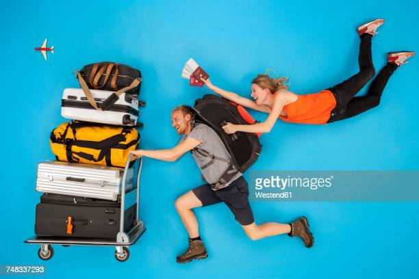 Couple with luggage trolley hurrying for departure