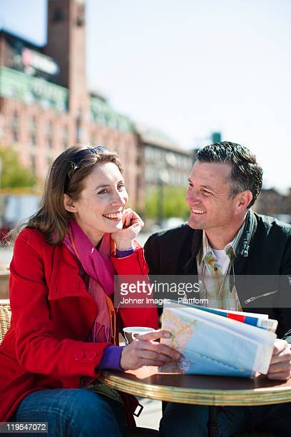 Couple with map at outdoor cafe in city