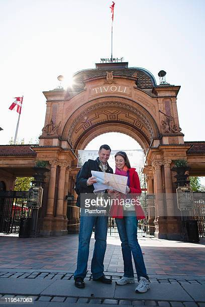 Couple with map sightseeing near arch