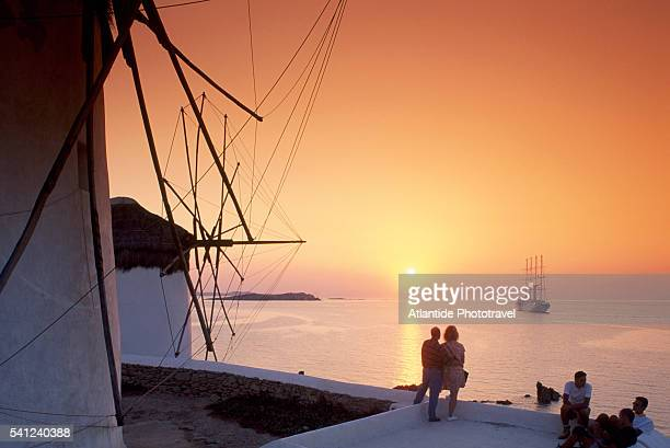 Couple With Mikonos Windmills at Sunset