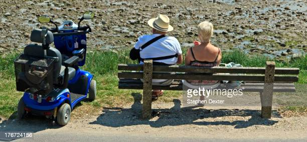 Couple, with mobility scooter, resting on a bench overlooking Swansea Bay in South Wales. This is on the route of the defunct Mumbles Railway, which...
