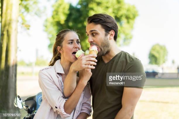 couple with motor scooter in summer sharing ice cream - eis essen stock-fotos und bilder
