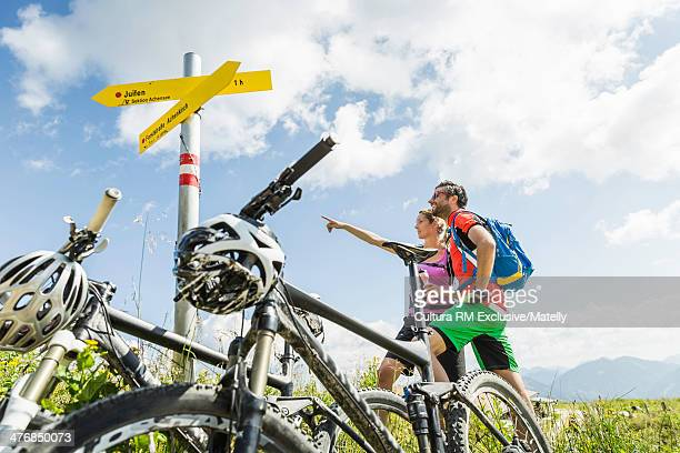 Couple with mountain bikes by direction sign, Tyrol, Austria