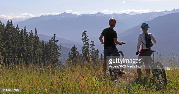 couple with mountain bikes pause on an alpine meadow above the mountains and look out - look back at early colour photography imagens e fotografias de stock