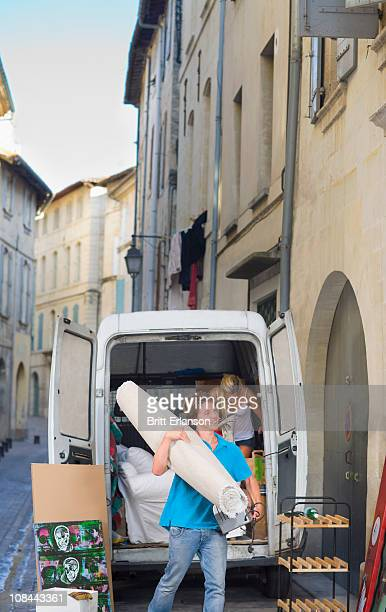 Couple with moving truck carrying rug
