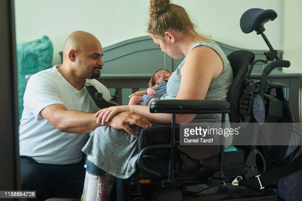 couple with newborn baby, mother is disabled. - disabilitycollection stock pictures, royalty-free photos & images