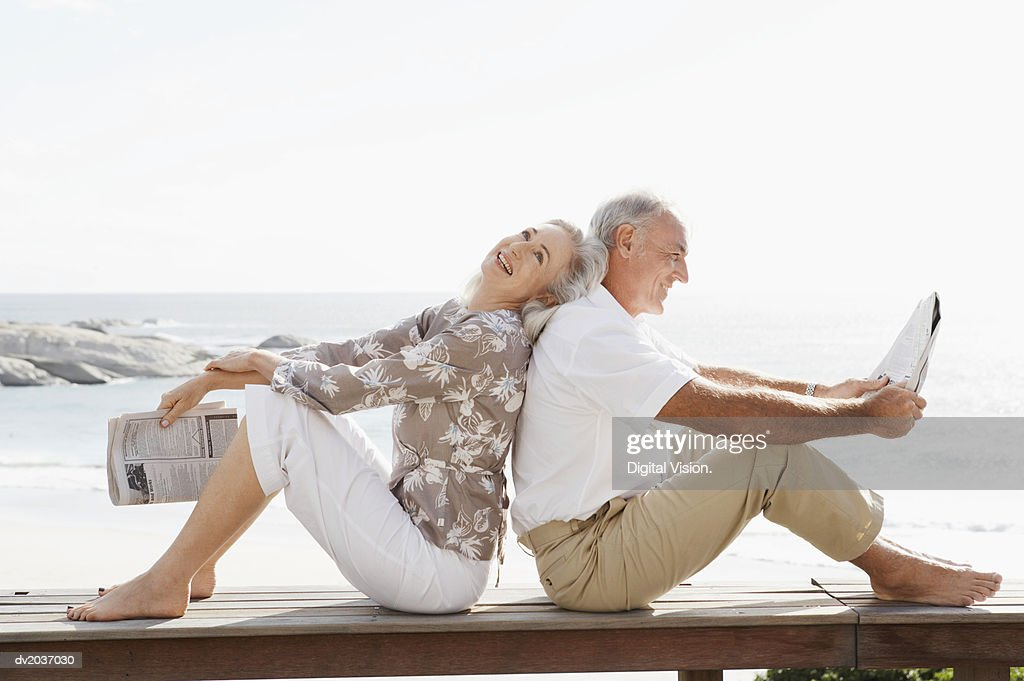 Couple With Newspapers Sitting Back to Back on Wooden Decking on the Coast : Stock Photo
