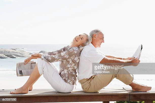 Couple With Newspapers Sitting Back to Back on Wooden Decking on the Coast