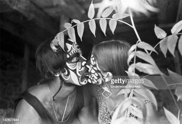 Couple with painted faces touch tongues in the shrubbery, California, late 1960s.