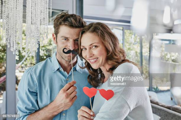 Couple with paper moustache and heart-shaped eye disguise