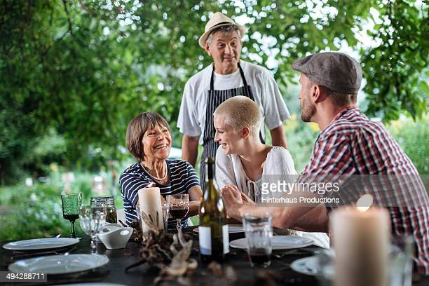 Couple With Parents Dining At Garden
