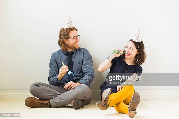 Couple with party horn blowers and party hats sitting on floor