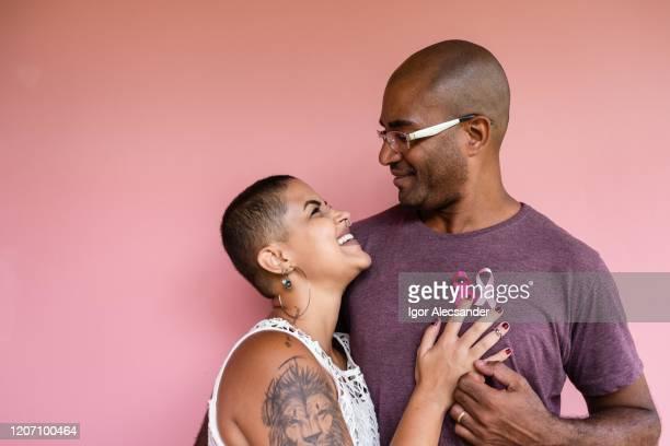 シャツにピンクの10月のリボンを持つカップル - 十月 ストックフォトと画像