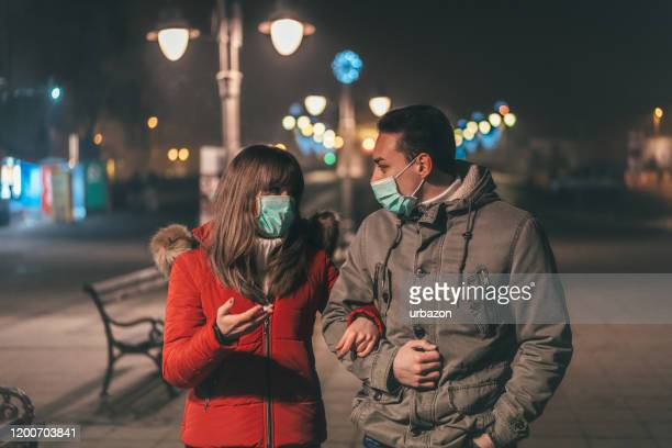 通りを歩く汚染マスクを持つカップル - お面 ストックフォトと画像