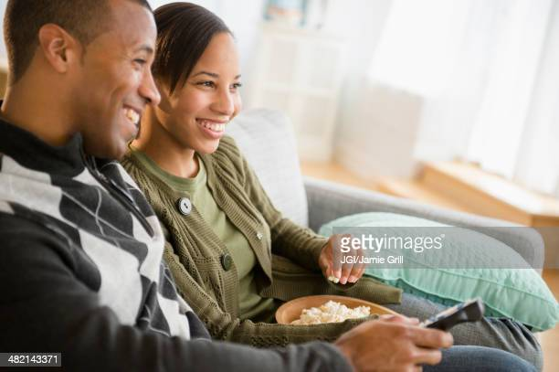 Couple with popcorn watching TV in living room