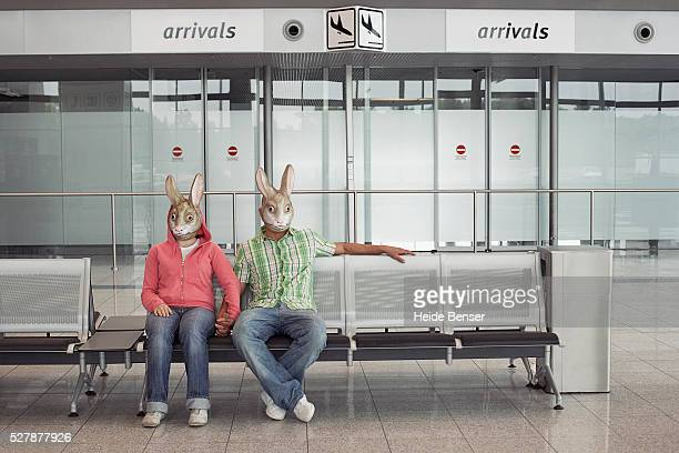 couple with rabbit masks sitting on bench in airport - rabbit mask stock pictures, royalty-free photos & images