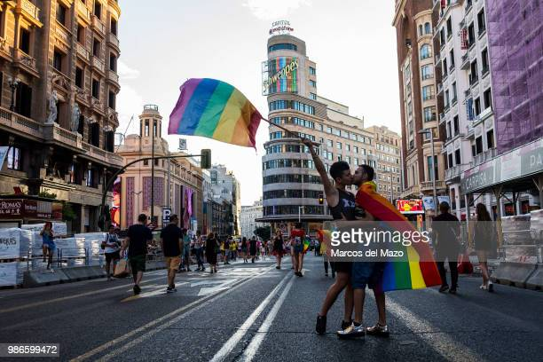 A couple with rainbow flags kiss each other in Gran Via street during a demonstration known as the 'Critical Pride' where LGBT community rally was...