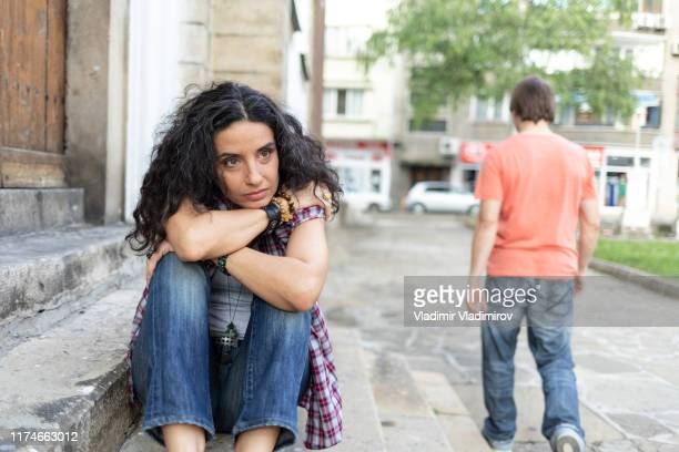 couple with relationship problems sitting on street - broken heart stock pictures, royalty-free photos & images