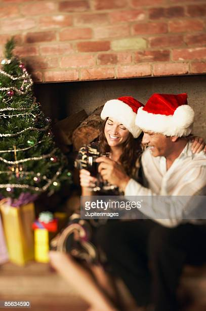 Couple with Santa Claus hats toasting with red wine