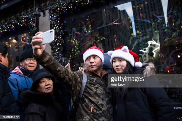 A couple with Santa hat pose for a photo near a store decoration on Fifth Avenue on Christmas day on December 25 2017 in New York CitySecurity in New...
