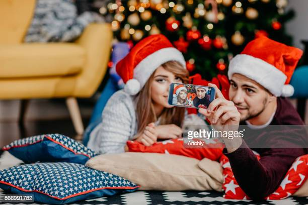 Couple with santa hats taking selfie in front of decorated christmas tree