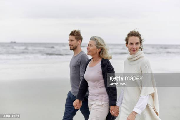 couple with senior woman walking on the beach - mother in law stock pictures, royalty-free photos & images