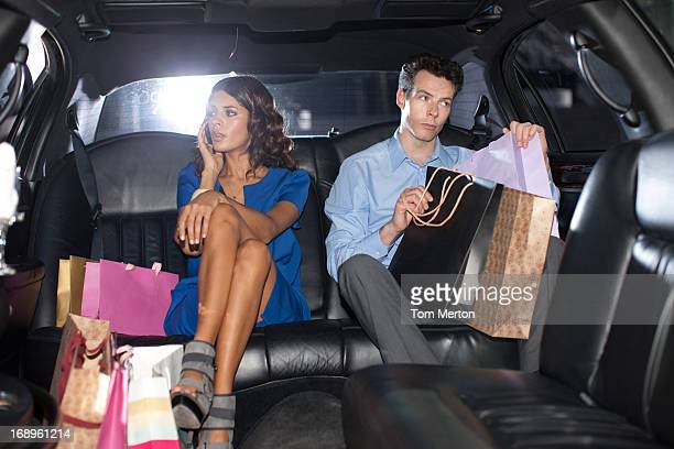 Couple with shopping bags in backseat of limo