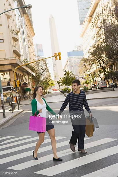 Couple with shopping bags in crosswalk