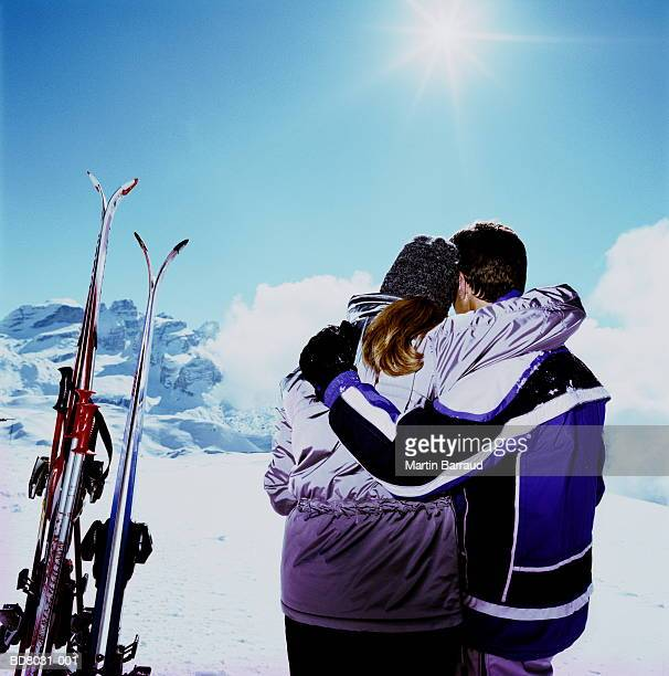 Couple with skis, arms around each other, rear view