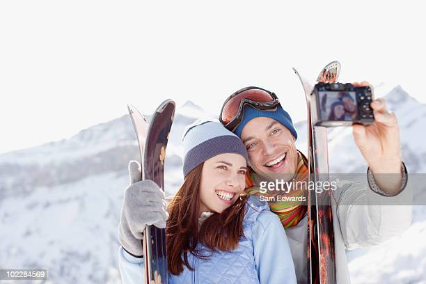 Couple with skis taking self-portrait