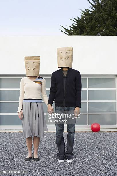 Couple with smiley face bags over heads holding hands in front of garage