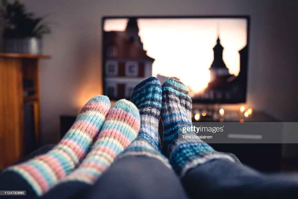 Couple with socks and woolen stockings watching movies or series on tv in winter. Woman and man sitting or lying together on sofa couch in home living room using online streaming service. : Stock Photo
