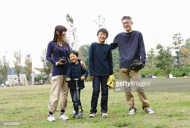 Couple with son and baby boy standing in park