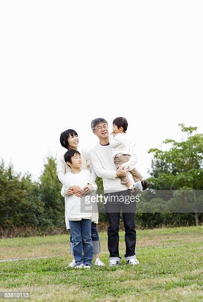 Couple with son and baby boy standing in park,port