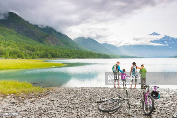 Couple with son and daughter riding bicycles near lake