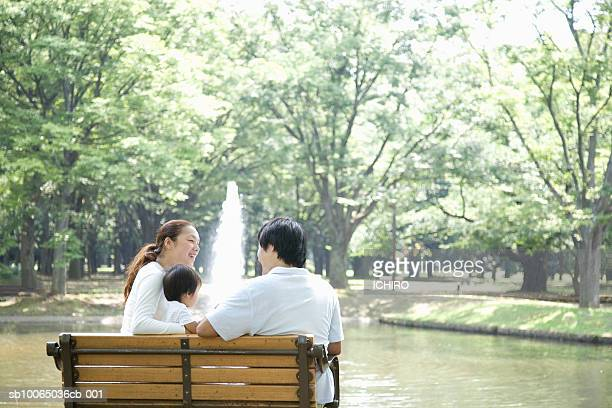 Couple with son (6-9 months) relaxing in park on bench, rear view