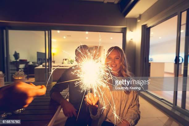Paar mit Wunderkerzen außerhalb Ihrer Hause bei Nacht.