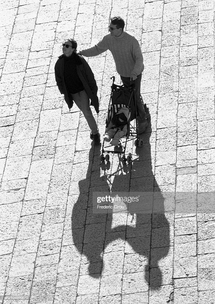 Couple with stroller walking on pavement, b&w : Stockfoto