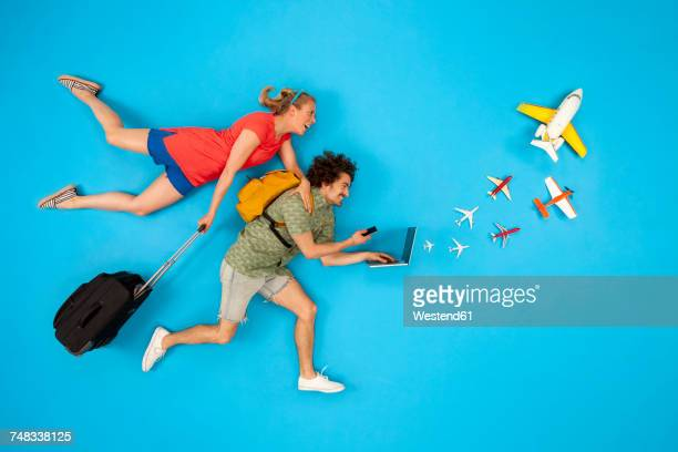 Couple with suitcase looking at laptop with airplanes coming out