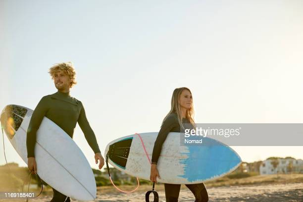 couple with surfboards at beach against clear sky - three quarter length stock pictures, royalty-free photos & images