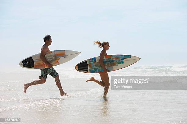 Couple with surfboards running on beach