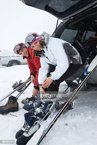 Couple with SUV and skis