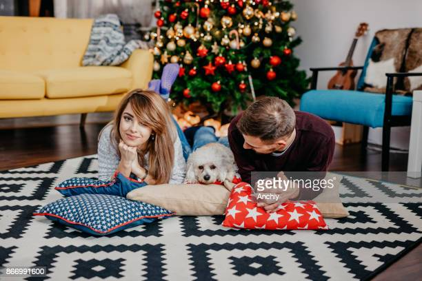 couple with the dog posing infront of decorated christmas tree