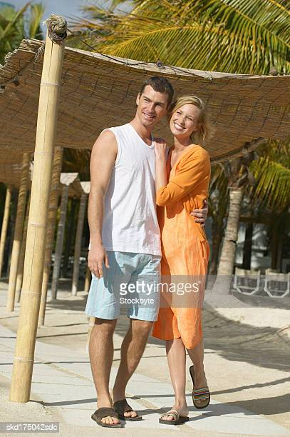 couple with their arms around each other standing on the beach