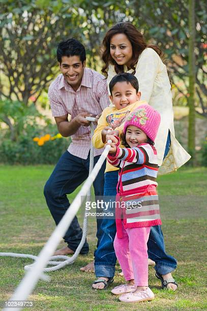 Couple with their children playing tug-of-war in a park