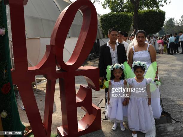 A couple with their children stand next to a LOVE decoration during a mass wedding in Manila on February 14 as part of Valentine's Day celebrations...