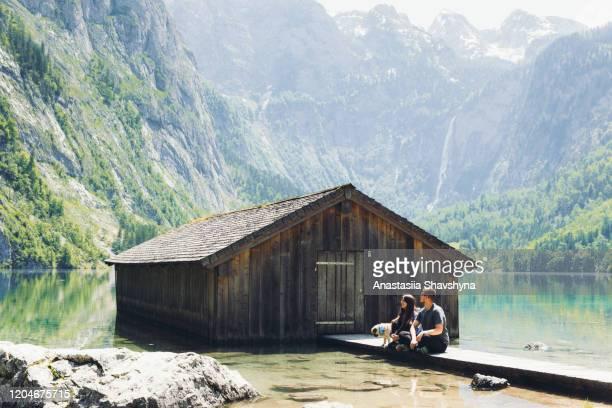 paar mit hund genießen den hellen sommer sonnenaufgang aufenthalt in der nähe der alten fischerhütte in bayerischen alpen - oberbayern stock-fotos und bilder