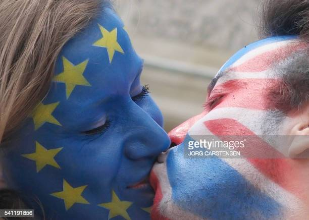 TOPSHOT A couple with their faces painted in the flags of the European Union and Great Britain kiss in front of the Brandenburg Gate in Berlin on...
